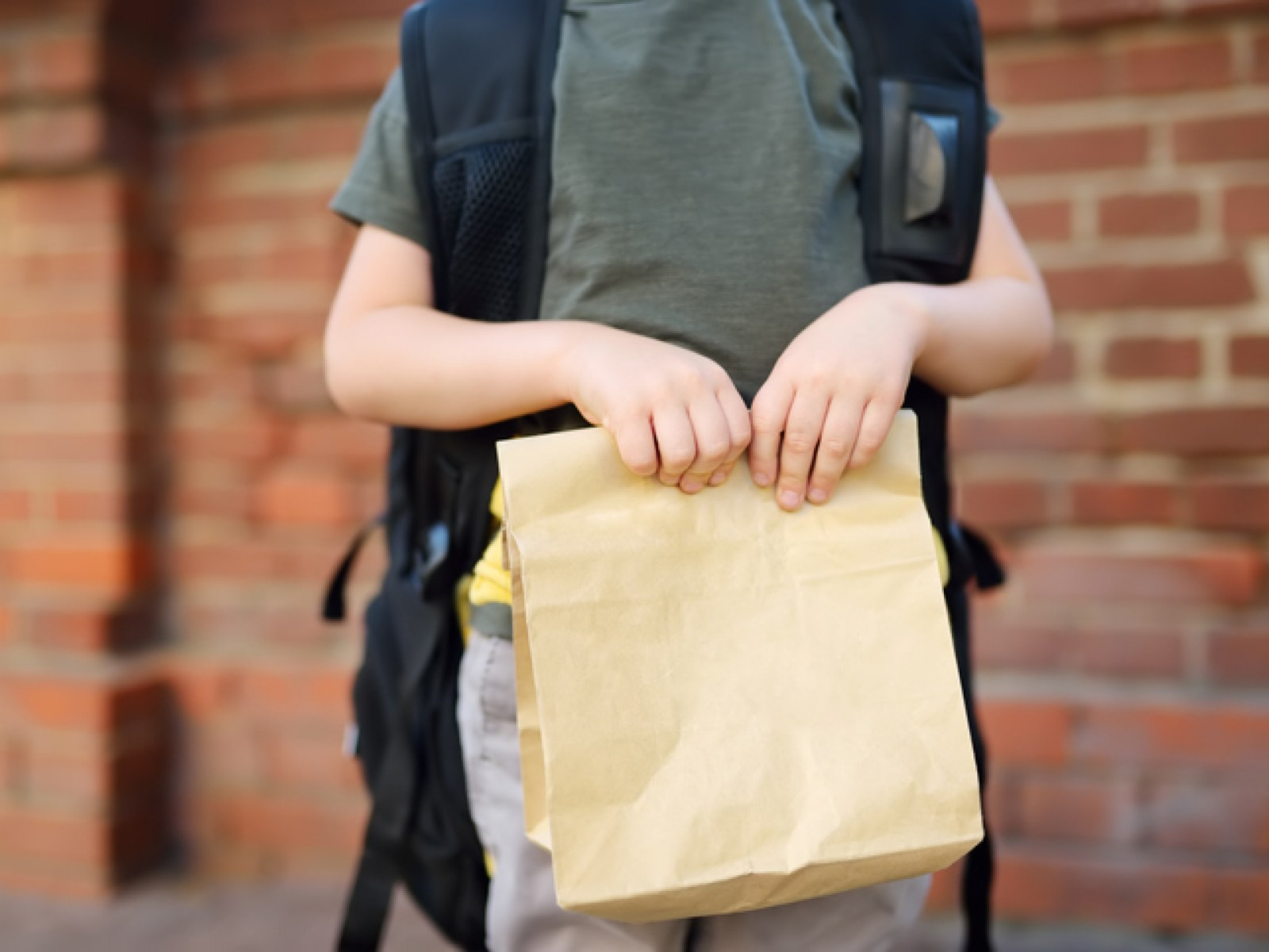 school-child-holding-sack-lunch
